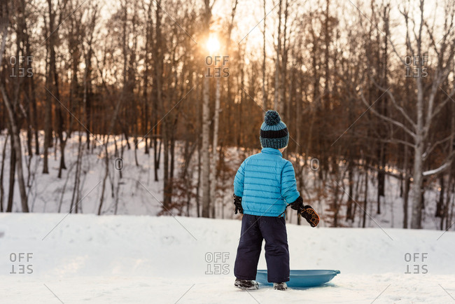 Boy standing next to sled on snow covered slope