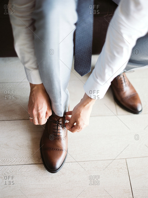 Man tying shoe for wedding