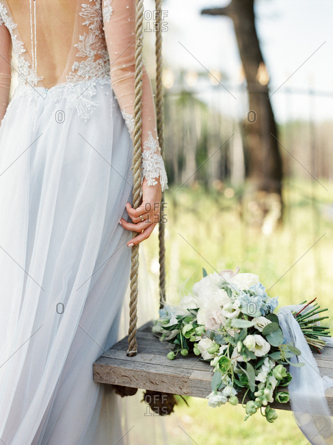 Bride by bouquet on a swing