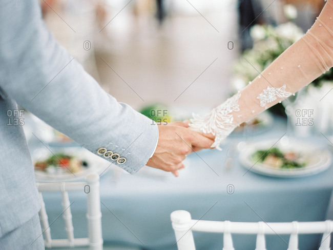 Bridal couple holding hands by reception table