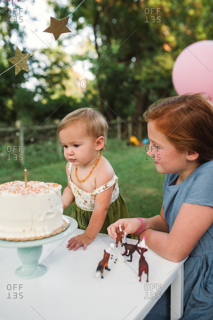 Girl watching toddler celebrate birthday