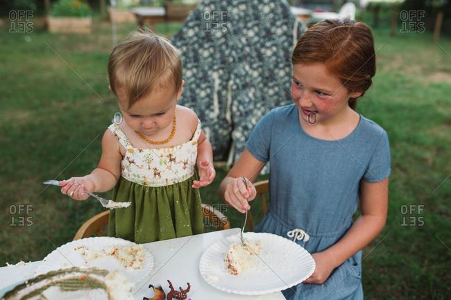 Girl and toddler eating cake outside