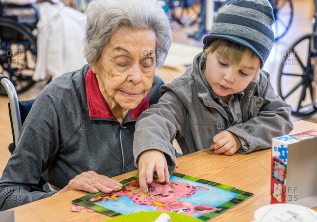 Boy and great grandma doing puzzle