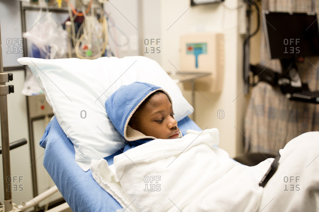 Boy lying in hospital using phone