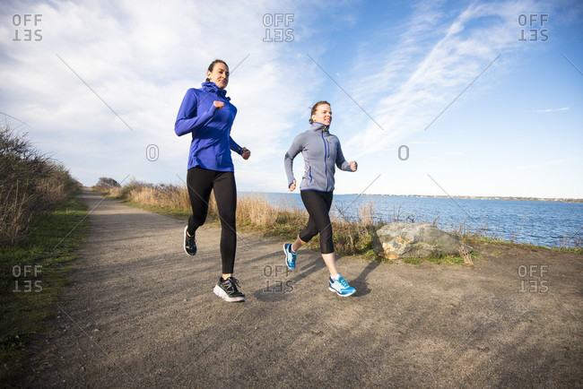 Women trail running together on a coastal path in Newport, Rhode Island, during early spring