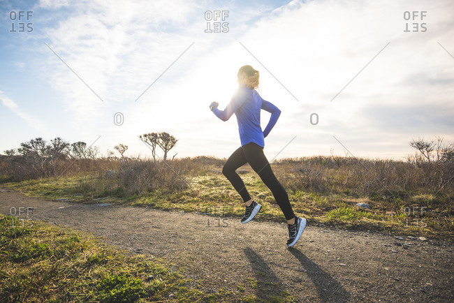 Woman trail running on a coastal path in Newport, Rhode Island, during early spring