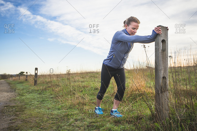 Woman stretching for a trail run on a coastal path in Newport, Rhode Island, during early spring