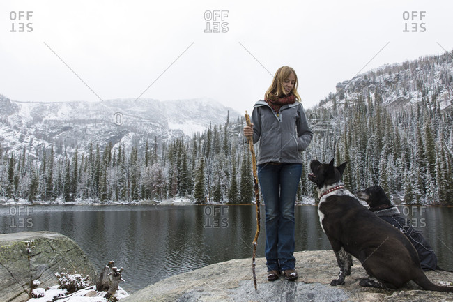 Woman with dogs hiking near lake in Bitterroot National Forest in winter, Montana, USA