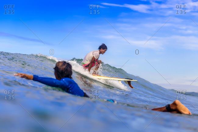 Man swimming beside surfer riding small wave, Kuta, Lombok, Indonesia