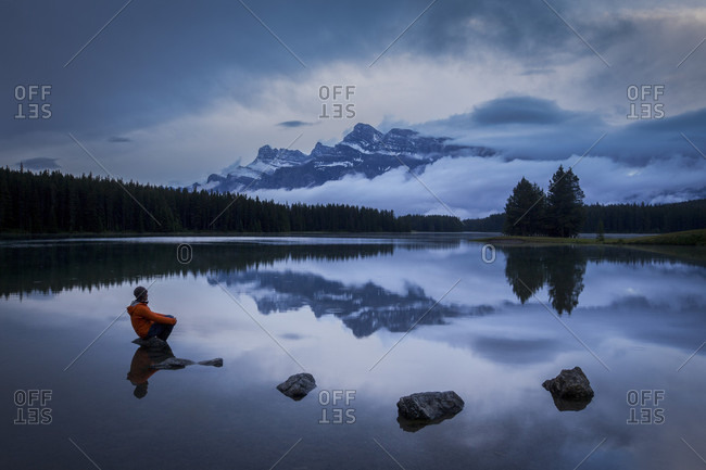 Beautiful scenery of Two Jack Lake with man sitting on rock at evening, Banff National Park, Alberta, Canada
