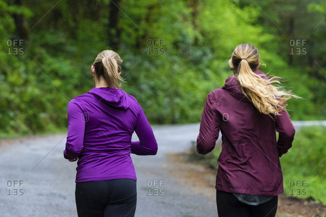 Rear view of two female joggers running on road in rain, Oregon, USA