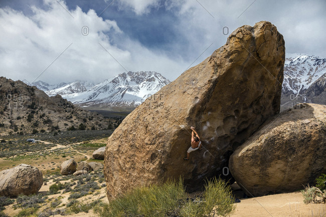 Young man climbing on rock formation, Bishop, California, USA