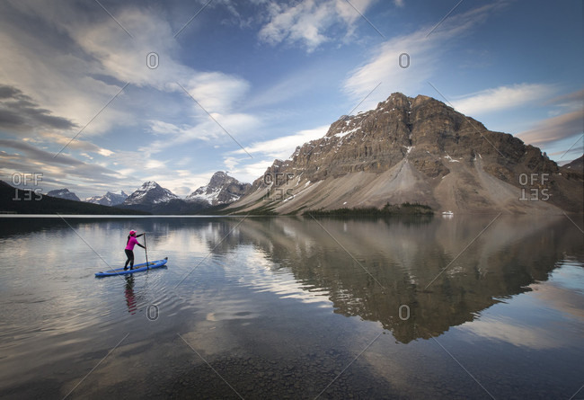 Photograph of woman paddleboarding in majestic scenery at Bow Lake, Banff National Park, Alberta, Canada