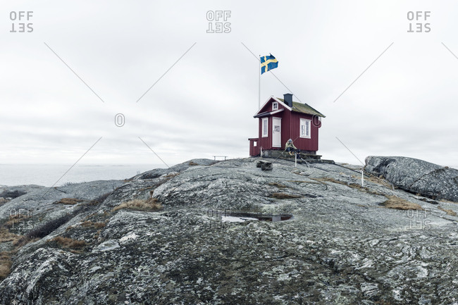 House on rock with Swedish flag