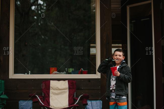 Boy brushing teeth by cabin