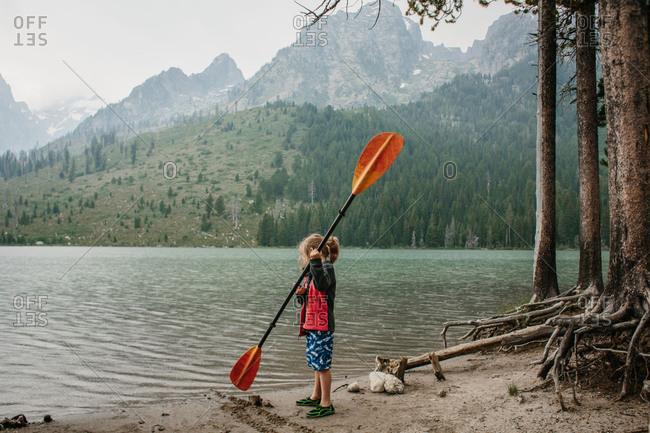 Boy with oar by mountain lake