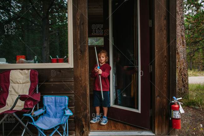 Boy with bow and arrow at cabin