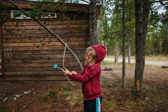 Boy with toy bow and arrow by cabin