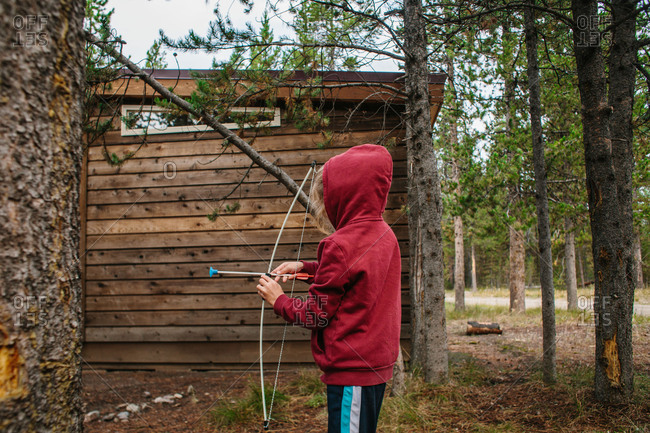 Boy with toy bow and arrow in woods