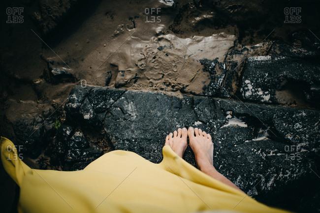 Girl on rocks among mud