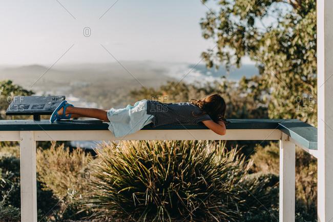 Girl lying on porch railing in Australia