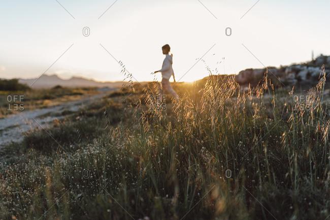 Girl exploring hills in sunlight