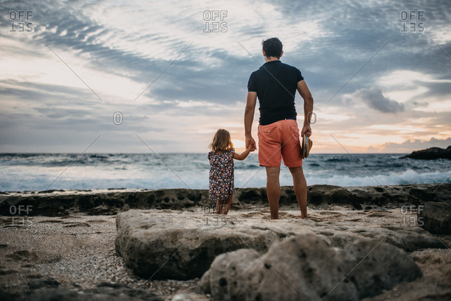 Girl and dad watching ocean waves