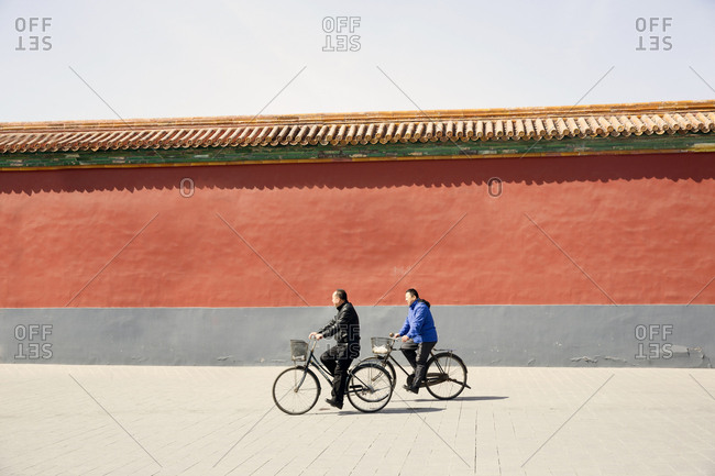 Beijing, China - March 16, 2016: Man riding bikes by Forbidden City