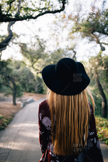 Young Woman with long blonde hair wearing a floppy black hat walking away from the camera on a path through the trees