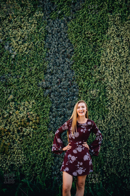 Well dressed young woman standing in front of a wall covered in succulents with her hands on her hips