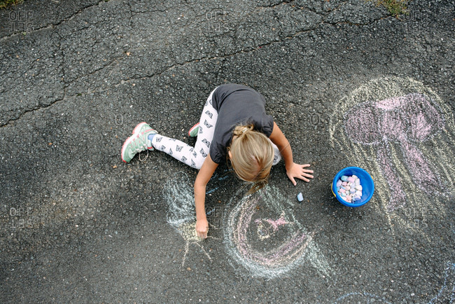Little girl making a chalk drawing on the street