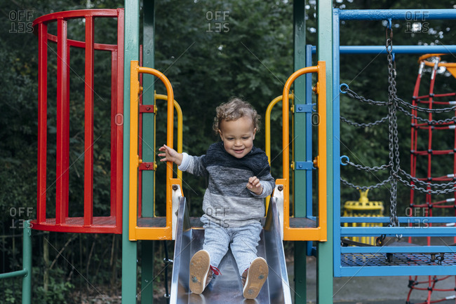 Smiling young boy sitting alone on a slide