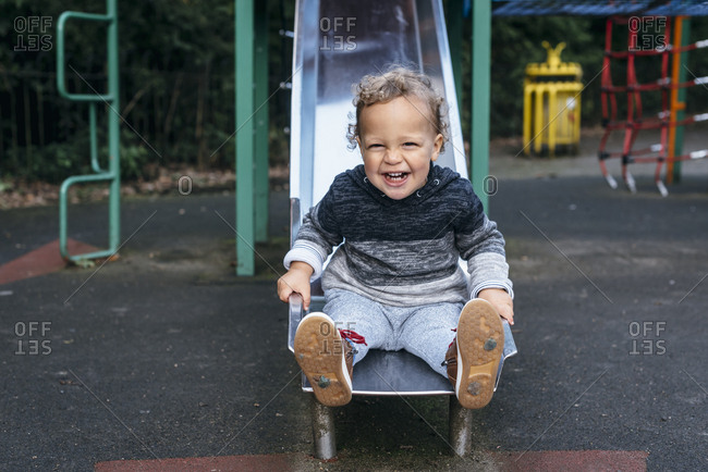 Laughing young boy sitting alone at the end of a slide
