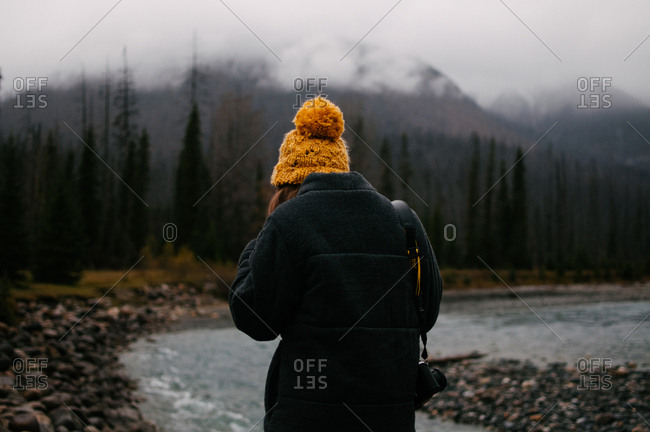 Woman with camera by mountain river