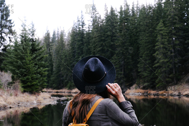 Woman in hat by forest river