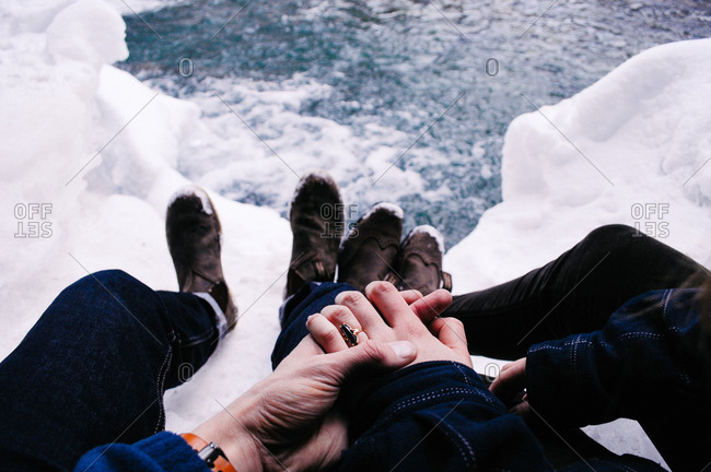 Couple holding hands by snow