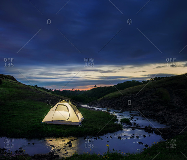 Camping tent beside a stream at the bottom of rolling hills in the mountains of northern California in the evening
