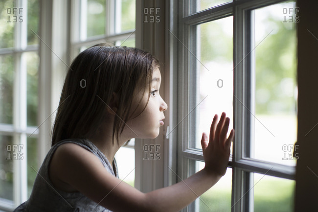 Young girl looking out window and touching glass