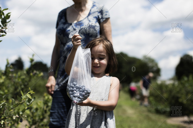 Young girl holding a bag full of blueberries on a farm