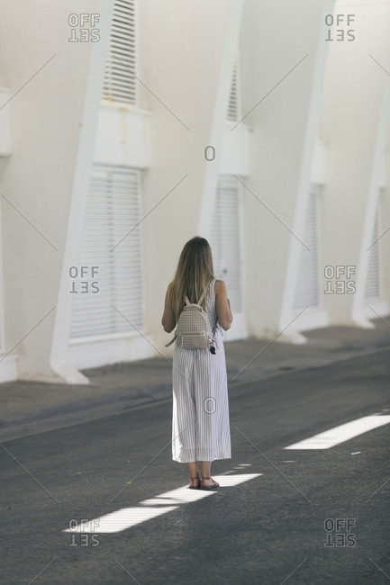Rear view of woman with long hair wearing striped outfit in Seville, Spain