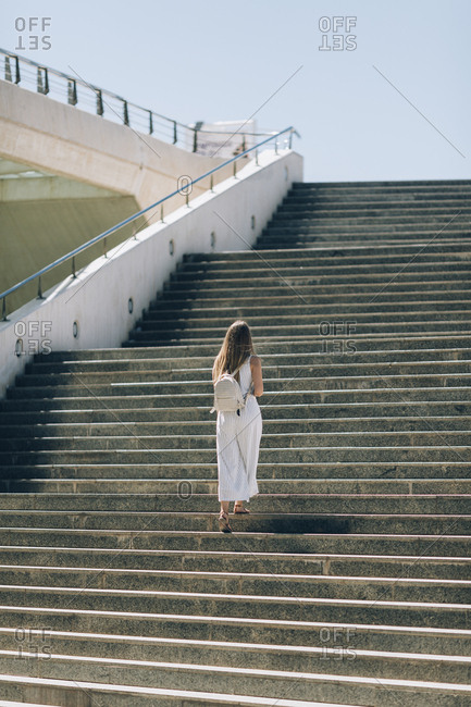 Woman with long hair walking up stairs in Seville, Spain