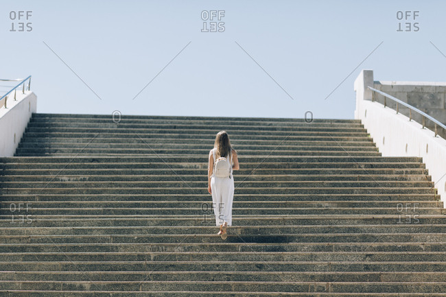 Rear view of woman with long hair walking up stairs in Seville, Spain