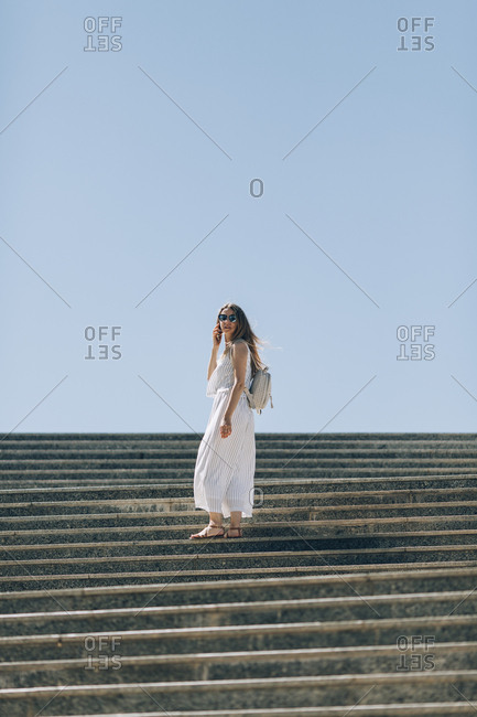 Woman standing on stairs using cell phone in Seville, Spain