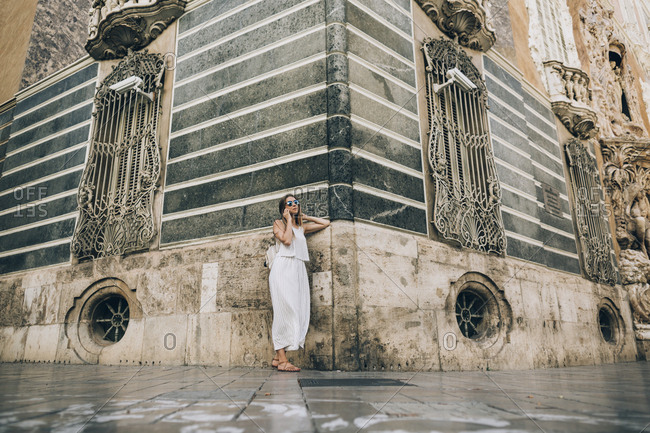 Woman leaning on old building and using phone in Seville, Spain