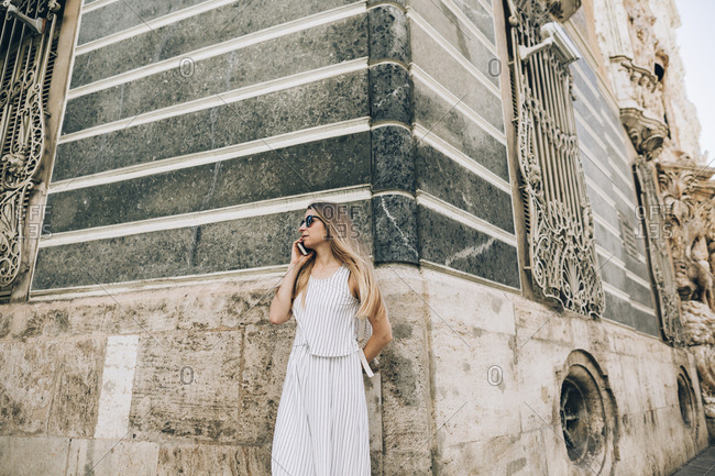 Woman standing by old building and using phone in Seville, Spain