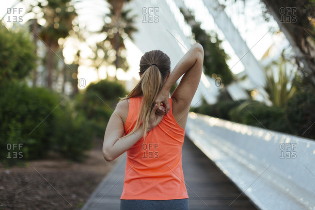 Woman stretching her arms behind her back before a workout