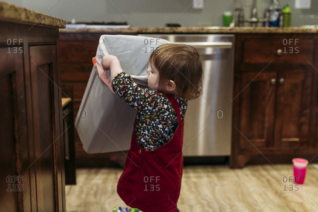 Toddler girl replacing trash can