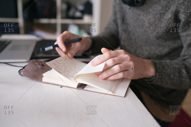 Hands of man flipping through journal pages