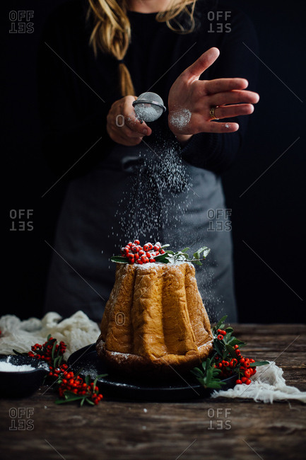 Woman sprinkling powdered sugar over a holiday cake