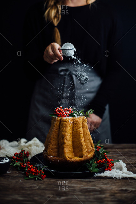 Woman topping holiday cake with powdered sugar